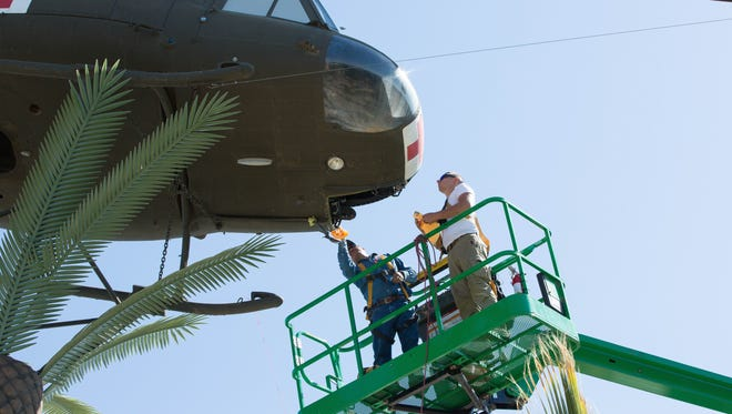 Hector Rodriguez, left, with the Las Cruces Parks and Recreation Department, and George W. Hayduke, a volunteer, work on replacing the chin bubble and windshield of the UH-1 Iroquois helicopter that is part of the Vietnam War Memorial at Veterans Memorial Park, Monday July 23, 2018. Repairs will cost about $20,000.