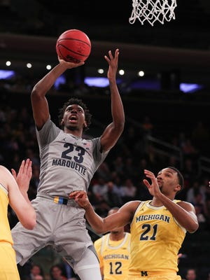 Marquette guard Jajuan Johnson shoots in front of Michigan guard Zak Irvin (21) in the first half of the Golden Eagles' 79-61 loss to the Wolverines on Thursday at Madison Square Garden.