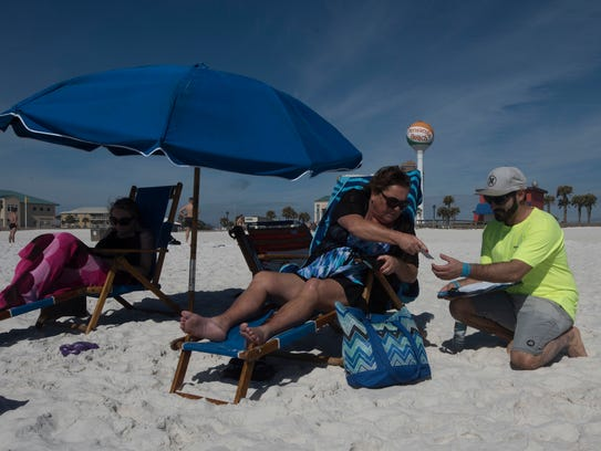 Patti Coote, center, rents her beach chair from Nick