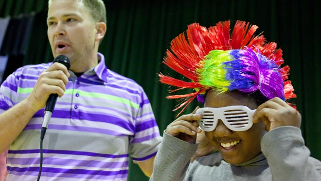 Fifth grade student Curvon Woodson, 11, puts on a wig and sunglasses before having a dance-off with author Lane Walker during an assembly at Kimball Elementary School.