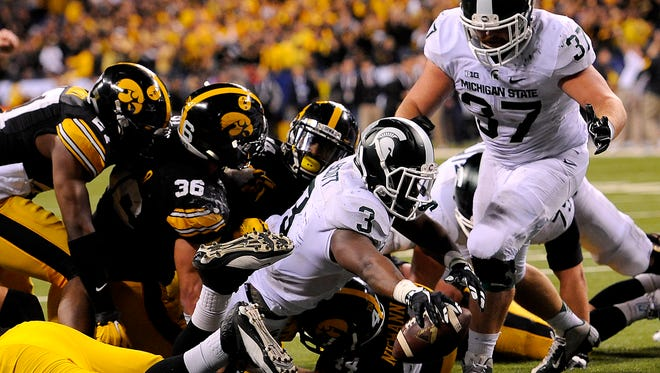 Running back LJ Scott reaches through a pile of Iowa defenders to stretch the ball across the goal line for the winning touchdown with 27 seconds left in the game December, 5, 2015, in Indianapolis in MSU's 16-13 win over Iowa in the Big Ten Championship football game.