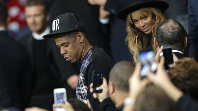 Jay Z and his wife Beyonce leave their seats at half time in the Champions League soccer match between PSG and Barcelona, at the Parc des Princes stadium, in Paris, Tuesday, Sept. 30, 2014.