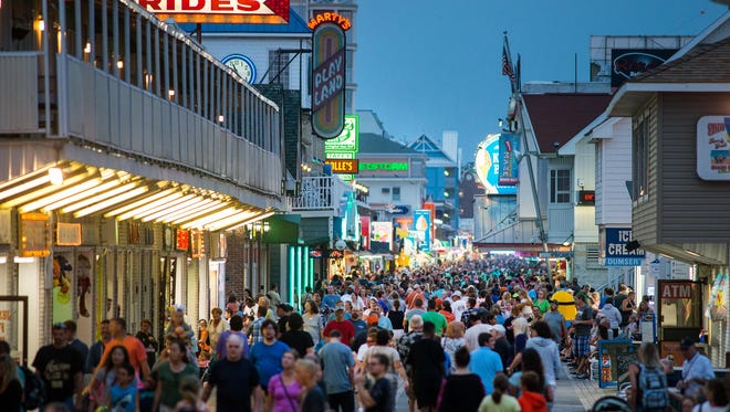 The Boardwalk in Ocean City bustles at with people moving about and performers entertaining passers-by.
