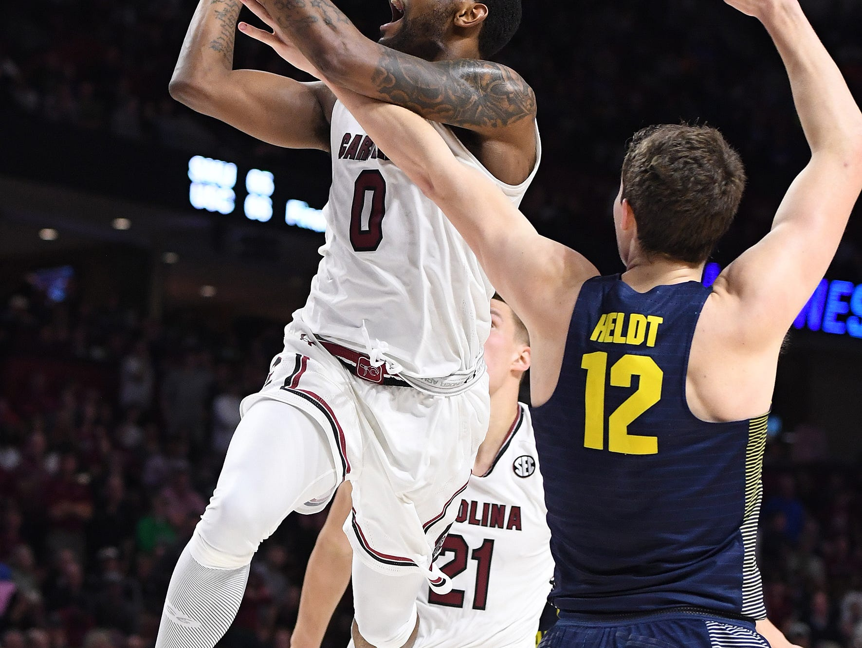 Marquette center Matt Heldt (12) fouls South Carolina guard Sindarius Thornwell (0) during the 1st round of the NCAA Tournament at Bon Secours Wellness Arena in downtown Greenville on Friday, March 17, 2017.