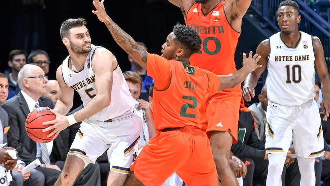 Notre Dame Fighting Irish guard Matt Farrell (5) looks to pass against Miami Hurricanes guard Chris Lykes (2) and forward Dewan Huell (20) in the first half at the Purcell Pavilion.