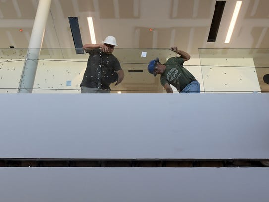 Construction workers install a glass panel on the second