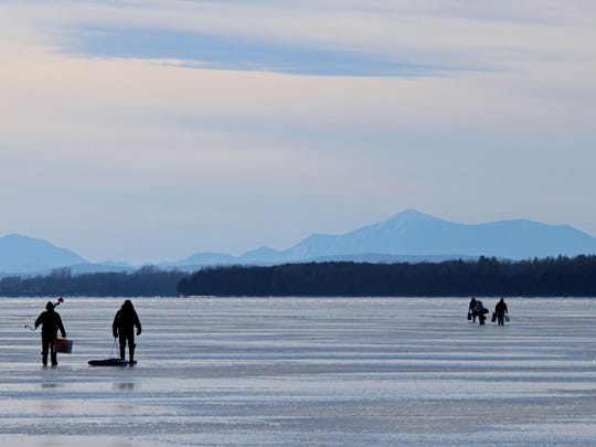 Ice fishing enthusiasts walk on Lake Champlain ice south of Sandbar State Park in Milton Thursday, January 19, 2012.