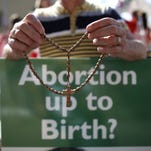 A protester holds rosary beads and an anti-abortion placard in front of the gates of the Irish Parliament building in Dublin on July 10, 2013.
