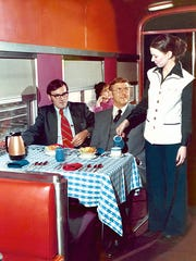 Amtrak dining car attendant Julie Byrne pours coffee for a customer in 1976 in a dining car that had been refurbished in a contemporary red and purple color scheme.