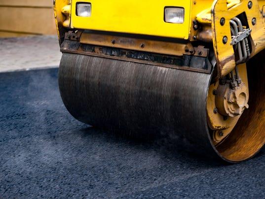 Compact steamroller flatten out the asphalt
