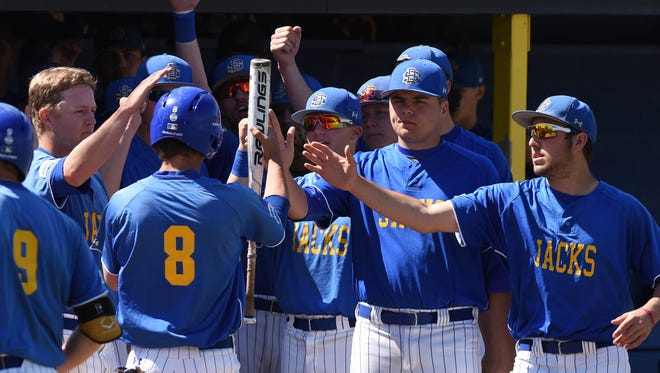 SDSU's Tony Kjolsing (8) is greeted by teammates after making it home against the University of Minnesota at Erv Huether Field in Brookings on Tuesday, May 17, 2016.