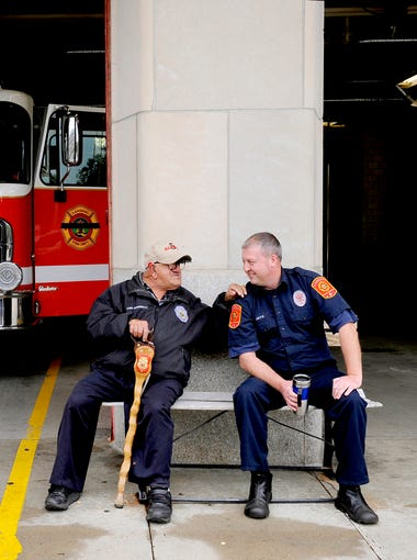 """Tony Tumminello, 75, leans on Lansing firefighter/paramedic Greg Smith as the two talk together in Tony's regular spot on a bench outside downtown Lansing's Fire Station One.  Tony has long been """"adopted"""" by firefighters at the station and has been a fixture there for 61 years, since Tony was 14.  Tony, who has been around for three generations of firefighters, eats with the crew, has his own locker, constantly jokes and tells the firefighters what to do, and shares a deep bond with all three platoons at the station.  The firefighters watch out for his welfare and  all pitch in to help take care of Tony.  """"We treat him like family,"""" says acting engineer Lisa McRae. """"To us, he is like family. Station life wouldn't be the same without him."""""""
