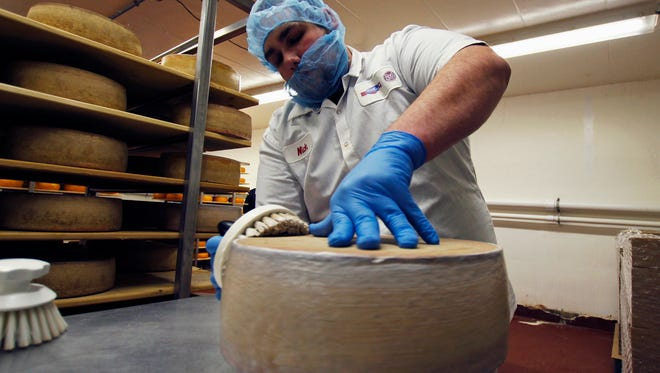 Nick Brummel prepares a wheel of Grand Cru Surchoix cheese at the Emmi Roth USA production plant in Monroe, WI, for labeling. The company won the World Championship Cheese Contest in 2016 for the cheese and since then has seen an increase in sales of the cheese.