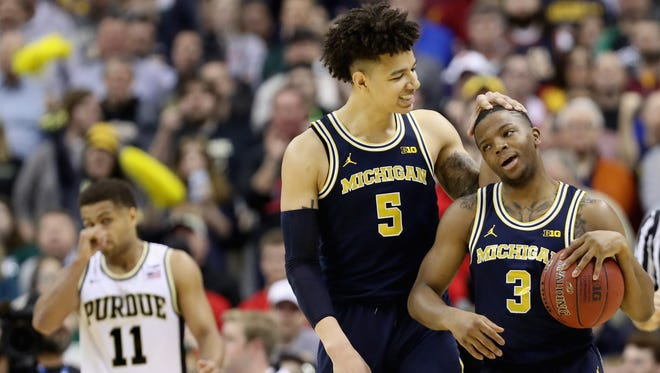 D.J. Wilson #5 and Xavier Simpson #3 of the Michigan Wolverines celebrate in the closing seconds of their 74-70 overtime win against the Purdue Boilermakers during the Big Ten Basketball Tournament at Verizon Center on March 10, 2017 in Washington, DC.
