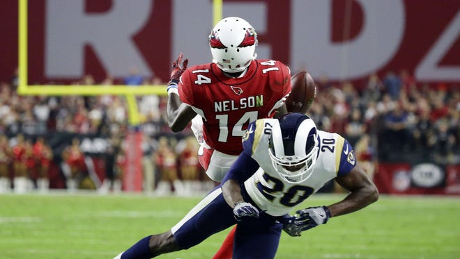 Arizona Cardinals J.J. Nelson loses the ball after being hit by Los Angeles Rams safety Lamarcus Joyner in the second half on Dec. 3, 2017 at University of Phoenix Stadium in Glendale, Ariz.