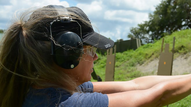 Jackie Follin of Naples prepares to fire her rented Glock. The Altair Gun Club held a Pistol 1 training course specifically for women on Saturday, July 16 at their shooting facility in Copeland.