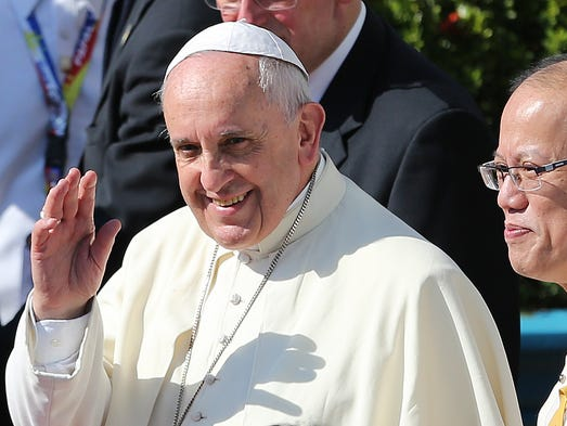 Pope Francis, left, waves to the crowd beside Philippine