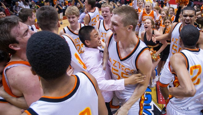 Tempe Corona del Sol's Connor MacDougall, middle, and teammates celebrate their win at the end of their Div. I boys basketball championship game against Phoenix Pinnacle at Jobing.com Arena on Saturday, March 1, 2014.
