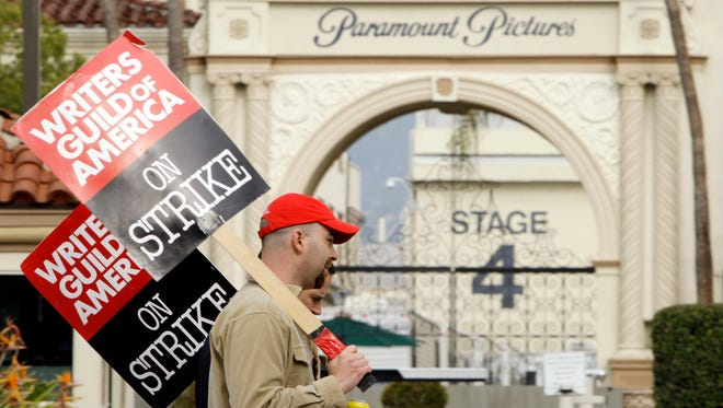 FILE - In this Jan. 23, 2008 file photo, striking film and television writers picket outside Paramount Studios in Los Angeles. Hollywood is facing a cliffhanger after members of the Writers Guild of America voted overwhelmingly to authorize a strike that could begin as soon as May 2, the day after the current contract ends. The previous writers' strike lasted 100 days in 2007-08 and was costly to the businesses that serve Hollywood and to consumers expecting to be entertained. (AP Photo/Kevork Djansezian, File)