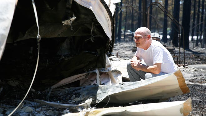 Rick Shepard holds back emotions as he stares at the charred remains of his trailer on Wilderness Drive in Eastpoint on Monday after a fire tore through the neighborhood the previous night. He fears about the fate of his cat Bunny, who he hopes made it out of the trailer alive.