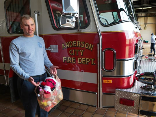 Firefighter Robbie Rhodes carries stuffed toys near a truck while working Christmas eve at the downtown fire station in Anderson. A stuffed toy is given to a child at an emergency scene, sometimes a car accident or a fire.
