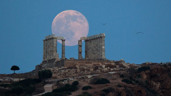 Seagulls fly as the full moon rises behind the ancient marble Temple of Poseidon at Cape Sounion, southeast of Athens, on the eve of the summer solstice on June 20, 2016.  The temple located on a promontory at Cape Sounion, about 45 miles south-southeast of Athens, built 444 BC, and dedicated to Poseidon, god of the sea.