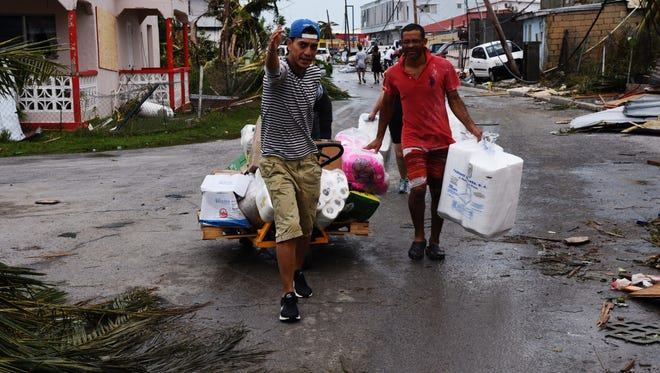 Hurricane Irma pummeled St. Maarten/St. Martin and other northern Caribbean islands Wednesday as it tore a disastrous path through the Atlantic toward the continental U.S. Here, these men wheel a cart of goods from a damaged warehouse through the streets of Cole Bay after the storm had passed. Local officials instituted a curfew to little effect. (D.A. Robin/Special to the Democrat)
