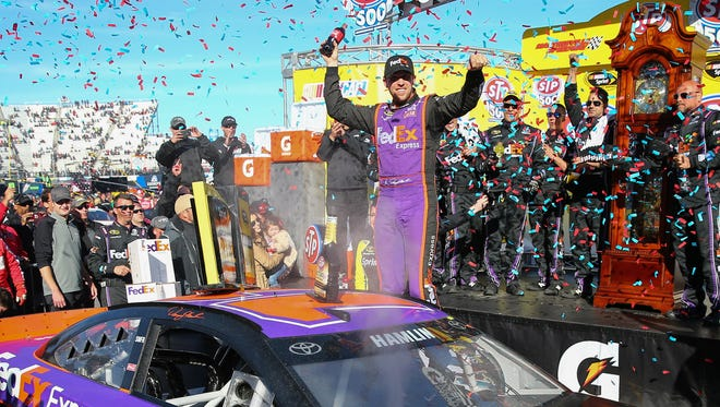 Denny Hamlin celebrates winning a fifth grandfather clock, in victory lane at Martinsville Speedway.
