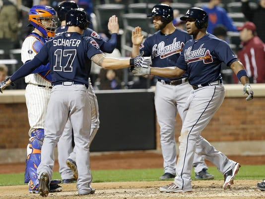 Atlanta Braves' Justin Upton, right celebrates with teammate Jordan Schafer (17) after hitting a three-run home run during the ninth inning of a baseball game against the New York Mets, Saturday, April 19, 2014, in New York. (AP Photo/Frank Franklin II)