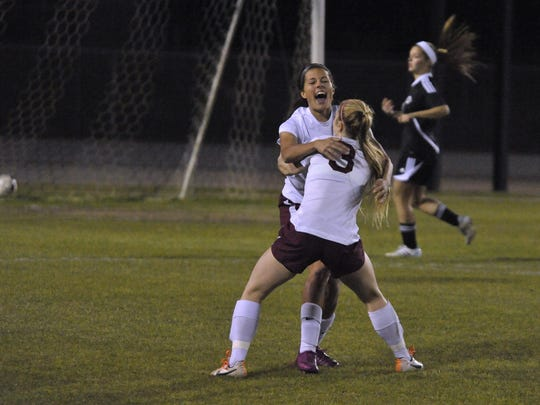 Emily Madril of Navarre celebrates with teammate Kayla Folse, front, after Madril scored the first goal against Creekside during their Region 1-4A title game at Navarre in 2015.