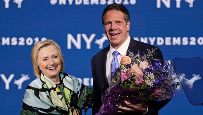 Former Secretary of State and former Democratic Presidential candidate Hillary Clinton, left, is greeted by Gov. Andrew Cuomo after speaking during the New York state Democratic convention after being greeted by New York Gov. Andrew Cuomo, Wednesday, May 23, 2018, in Hempstead, N.Y. (AP Photo/Julie Jacobson)
