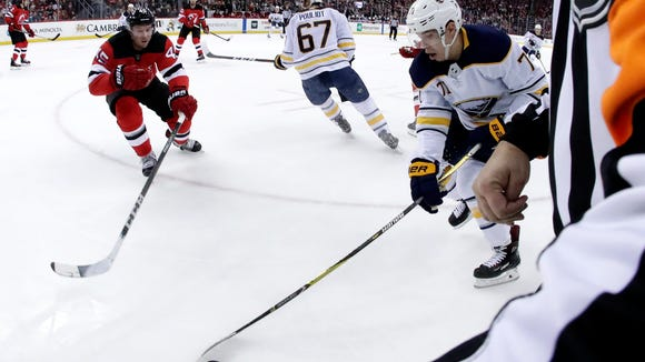 Buffalo Sabres left wing Evan Rodrigues (71) skates with the puck as New Jersey Devils defenseman Sami Vatanen (45), of Finland, tries to challenge him during the first period of an NHL hockey game, Friday, Dec. 29, 2017, in Newark, N.J. (AP Photo/Julio Cortez)
