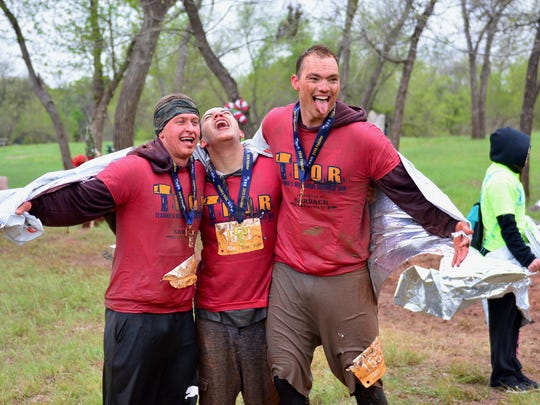 A medaled trio celebrate the successful T.H.O.R. completion of their late Saturday morning mud adventure.