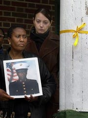 From left, Carmen Palmer holds a picture of her son, Marine corporal Bernard Gooden, in front of the Mount Vernon home where Elizabeth Knox, Gooden's fiance, had tied a yellow ribbon in his memory on April 8, 2003.