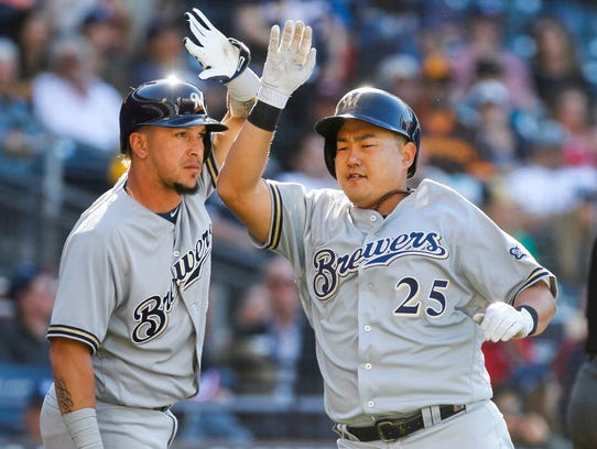 Ji-Man Choi (right) is congratulated by Hernan Perez after scoring in the 12th inning against the Padres on March 29 in San Diego.