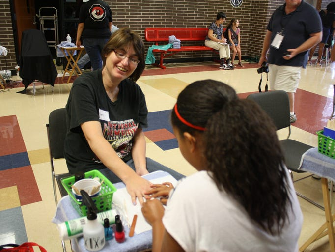 Mary Crim receives a manicure from Aija Estes, 11, in the spa area of the third annual Health and Wellness Fair at Jeffersonville High School hosted by Eastside Christian Church, Centerstone and Community Action of Southern Indiana on Saturday.  (By Jenna Esarey, special to The Courier-Journal)  July 12, 2014.