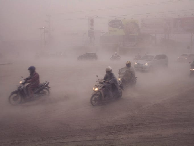 Volcanic ash swirls among motorcyclists in Yogyakarta, Indonesia on Feb. 14.