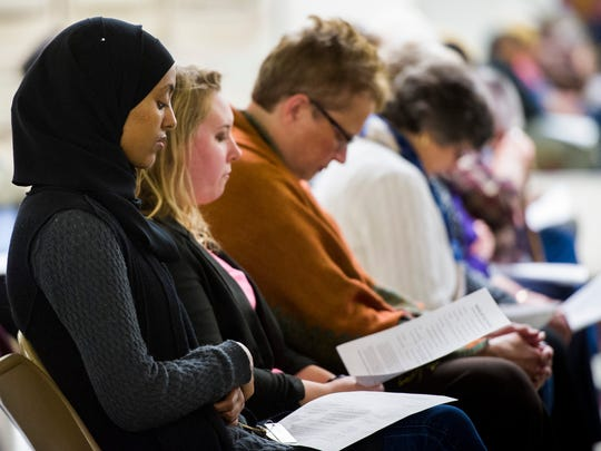"Fethia Mohamabe, of Newburgh, left,  attends ""Bridges, Not Walls,"" an interfaith prayer service held at C.K. Newsome Community Center in Evansville, Thursday, Nov. 10, 2016. Bridge, an interfaith group in Evansville sponsored the event in order to bring various communities together in faith."