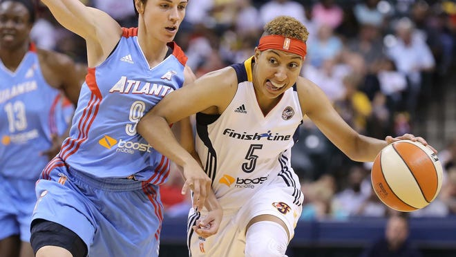 Layshia Clarendon of the Fever drives past Dream defender Celine Dumerc at mid-court. The Indiana Fever hosted the Atlanta Dream in WNBA action at Bankers Life Fieldhouse Sunday June 29, 2014.