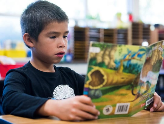 Second-grader Shawn Willis reads in class at Laura