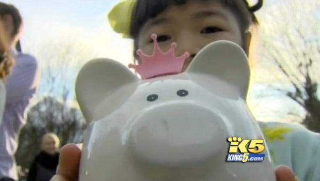 Anya Lin, 6, holds her piggy bank she donated for mudslide relief efforts in Washington.