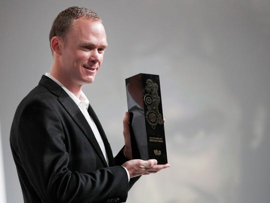 Britain's Chris Froome, centre, poses with his Velo d'Or award during the presentation of the 2018 Tour de France cycling race, in Paris, Tuesday Oct. 17, 2017. The 105th edition of the race starts on July 7 2018 to end on the Champs-Elysees avenue on July 29. French former cyclist Bernard Hinault stands at right. (AP Photo/Christophe Ena)