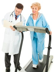 Senior woman exercising under a doctor's supervision.