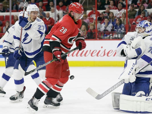 Tampa Bay Lightning goalie Louis Domingue (70) blocks Carolina Hurricanes' Elias Lindholm (28), of Sweden, while Lightning's Ryan McDonagh (27) looks on at left during the second period of an NHL hockey game in Raleigh, N.C., Saturday, April 7, 2018. (AP Photo/Gerry Broome)