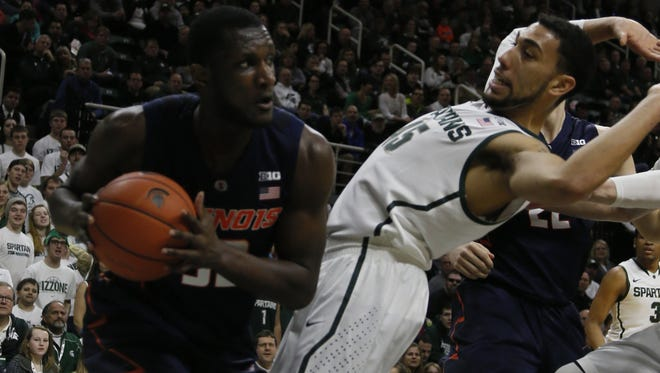 Michigan State's Denzel Valentine avoids a foul as Illinois' Nnanna Egwu grabs a defensive rebound in the first half on Saturday, Feb. 7, 2015, at the Breslin Center in East Lansing, Mich. The Fighting Illini won, 59-54.