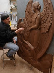 Jerry Williams work in clay to prepare for the final execution of a statue in granite.