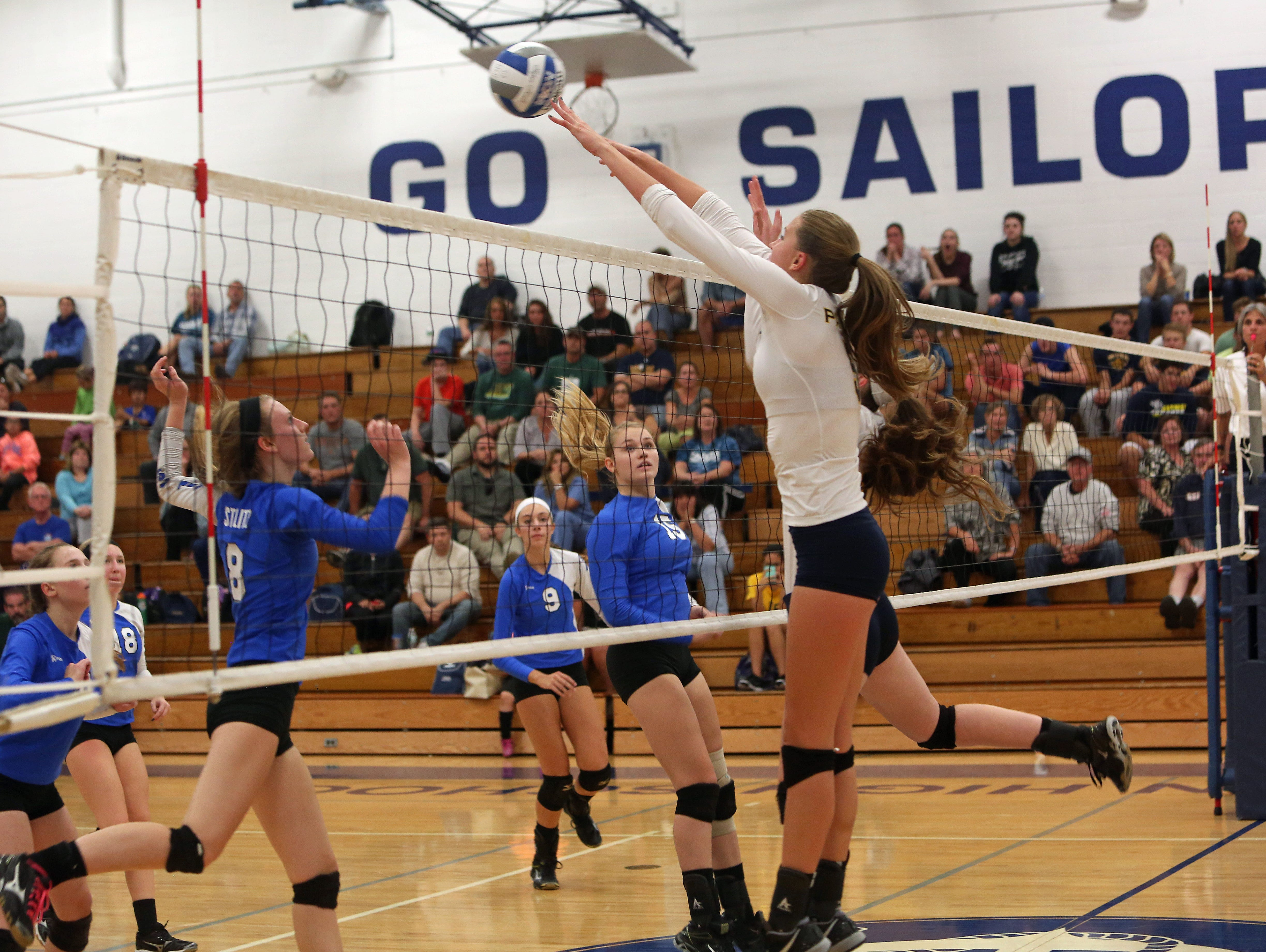 From right, Walter Panas' Yvette Burcescu (5) gets a shot by Hen Hud's Gillian Stieglitz (8) during volleyball action at Hendrick Hudson High School in Montrose Oct. 8, 2015. Panas swept the host 3-0.