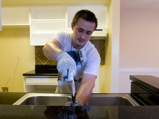 Vladimir Lysytsyn places a  faucet back together after the kitchen underwent renovations in the apartment unit Wednesday at The Park at Veneto in Fort Myers.