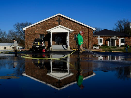"""Phillip Meredith (front) and Nick Payne (back) clean mud off of the parking lot in front of Beals Pentecostal Church, located at the intersection of Kentucky 811 and US-60 in Reed, Ky., Sunday evening. """"If you've lived here your whole life it's [flooding] just something you put up with,"""" said Meredith, who is a member of the church and lives in the area."""