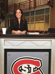 Katie Emmer sits at a desk before the pregame show